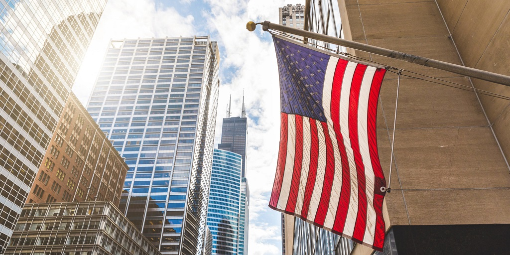 A photo of an American flag hanging outside downtown the city of Chicago with Sears Tower in the background.