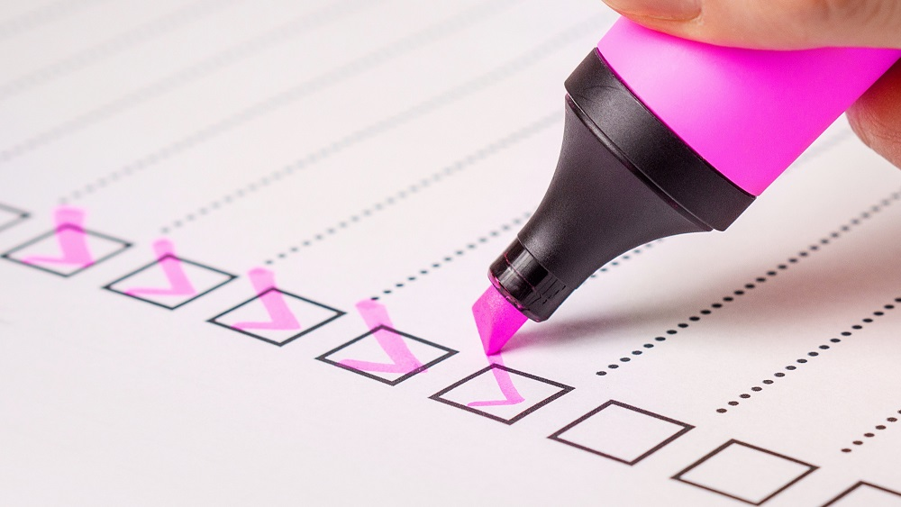 Marking off the checklist with a bright pink highlighter